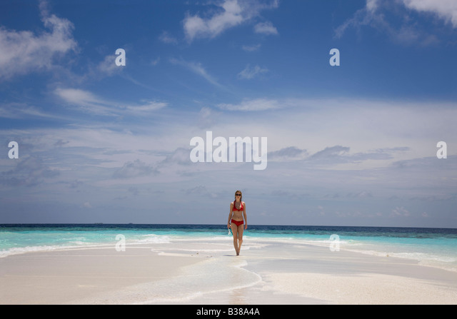 Young woman walking along deserted white sand beach surrounded by tropical waters in Maldives near India - Stock-Bilder
