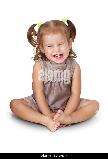 Sitting angry child girl with grin isolated on white - Stock Image