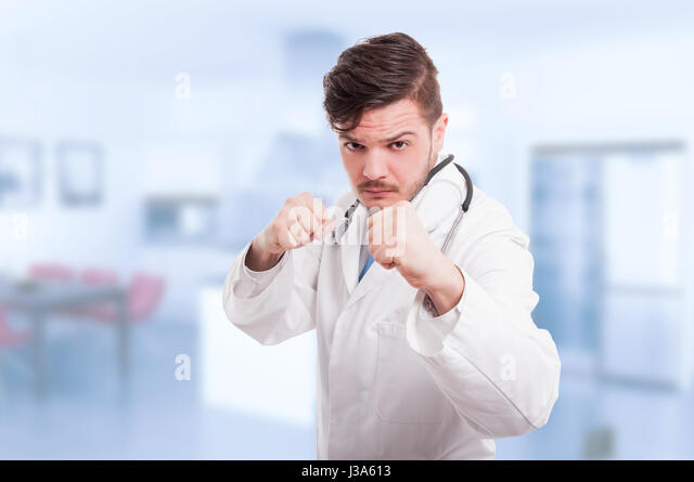 Doctor or medic acting violent and being ready to fight holding his fists up - Stock Image