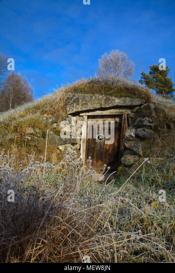 Wooden door to a traditional root cellar used for storing food supplies at a low temperature and steady humidity on a frosty autumn morning in Sweden. - Stock Image