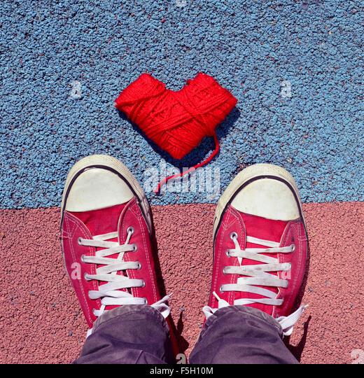 high-angle shot of a heart-shaped coil of red yarn and the feet of a man wearing red sneakers stepping on the asphalt - Stock Image