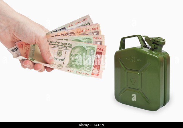 Many diverse Indian rupee bills are held in the hand. Near by is a green 5 liters gasoline canister of metal, background - Stock-Bilder