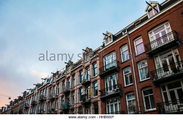 Amsterdam housefronts in winter with blue and orange sky - Stock Image