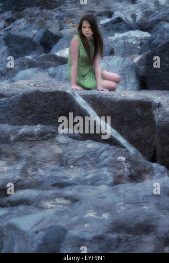 a girl in a floral dress is sitting on stones - Stock Image
