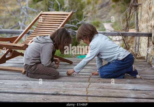 Brother and sister making a row of dried beans on balcony - Stock Image
