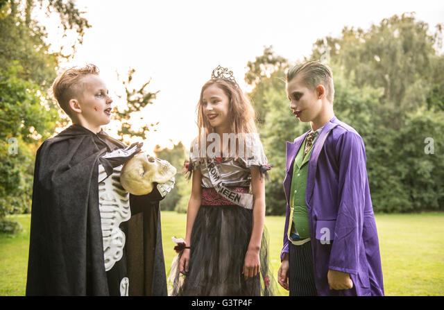 Three children dressed in costume for Halloween Night. - Stock Image