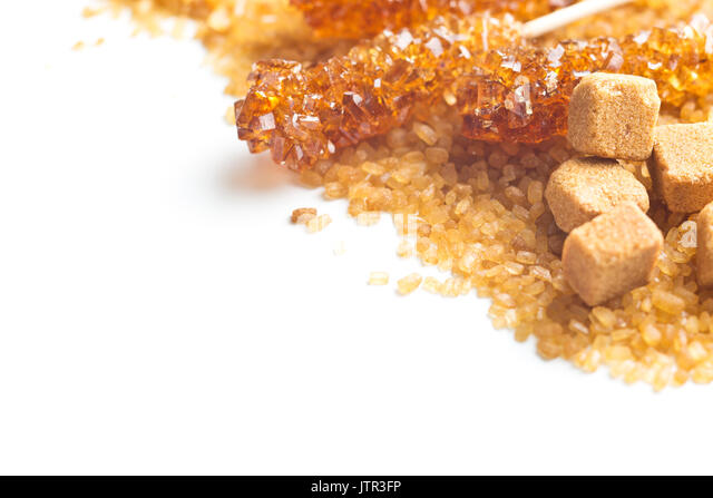 Brown cane sugar, cube sugar and crystalline sugar on wooden sticks isolated on white background. - Stock Image