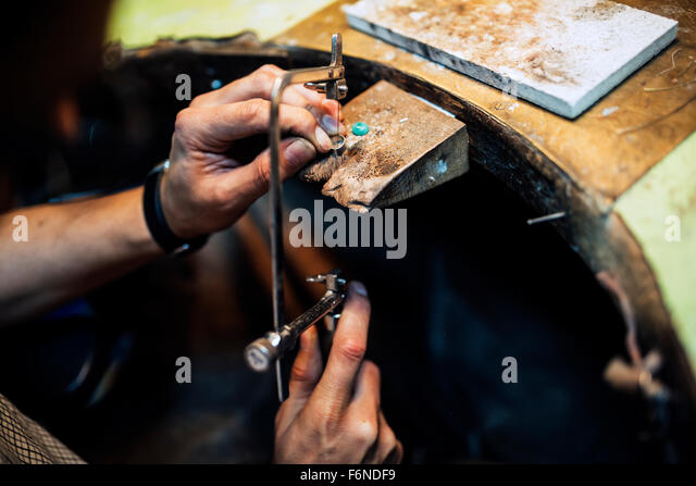 Jeweler using saw to create jewelry - Stock Image