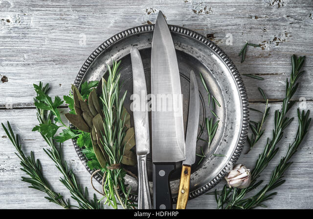 Metal plate with knifes and different  herbs on the white table top view - Stock Image