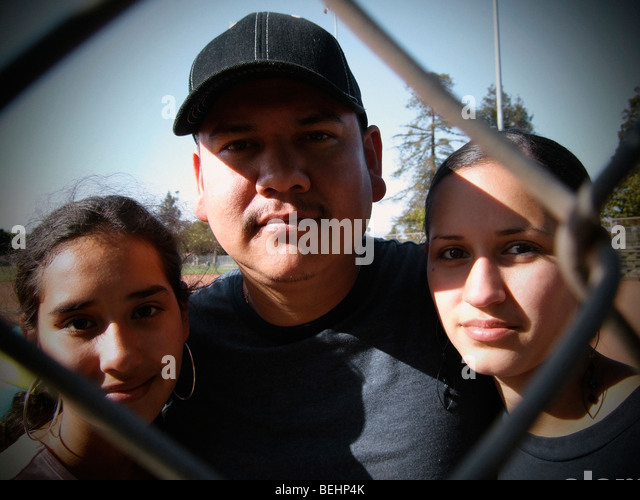 Father with two daughters looking through baseball fence - Stock-Bilder