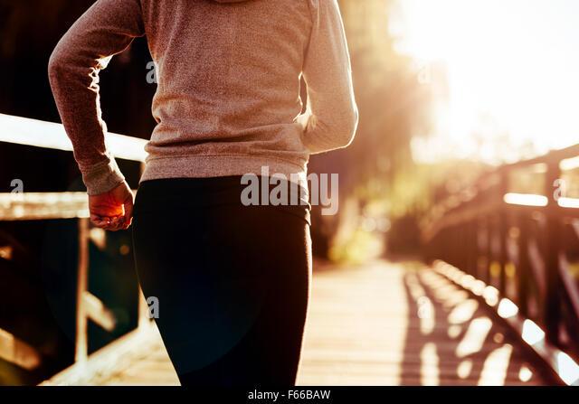Beautiful female runner jogging in nature - Stock Image