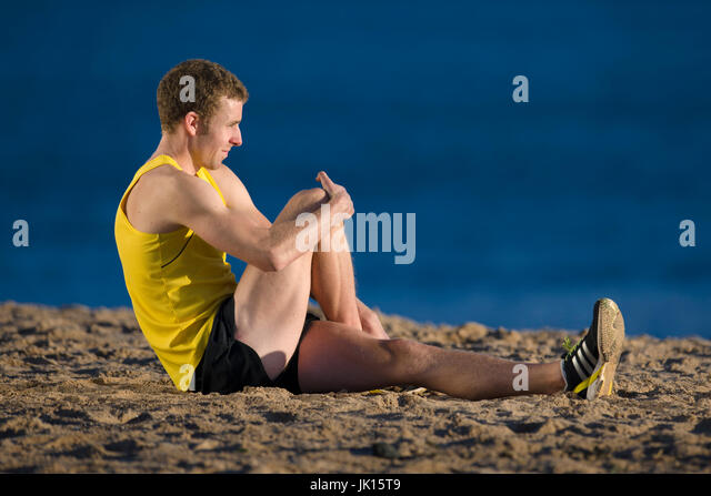 Runner stretching gluteus maximus muscles, knee to chest, buttocks stretch. - Stock Image