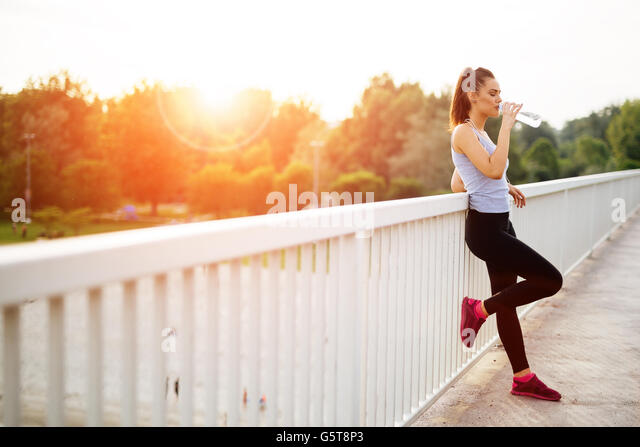 Woman drinking water after running session - Stock Image