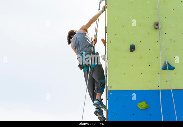 Bologna,Italy-May 31,2015:an athlete climbing on an artificial wall for training during a cloudy day - Stock Image