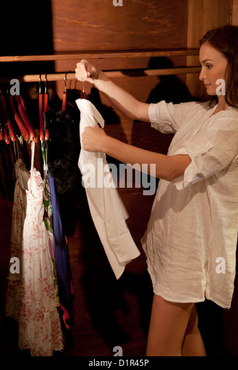 woman chooses a dress from the wardrobe - Stock Image