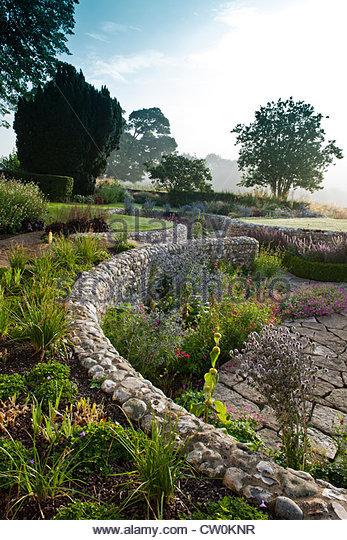 contemporary sunken garden stone walls retaining designer design Julie Toll curved circular sinuous patio summer - Stock Image