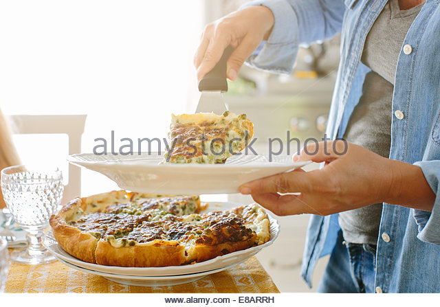 Woman holding plate serving flan - Stock Image