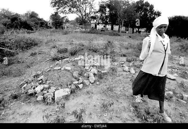 AIDS, poverty and drought in rural areas of Kenya. Kenyan woman. Her husband is buried in the garden. In Kitui families - Stock Image