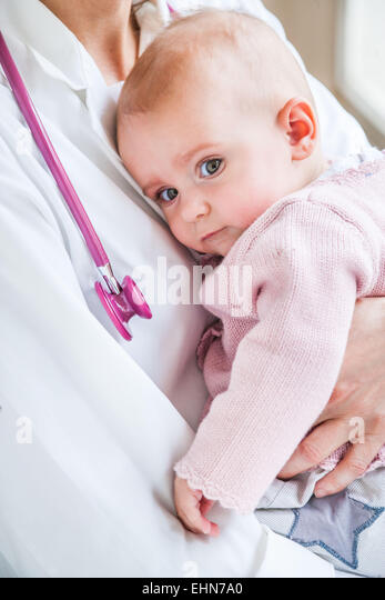 7-month-old baby girl with pediatrician. - Stock Image