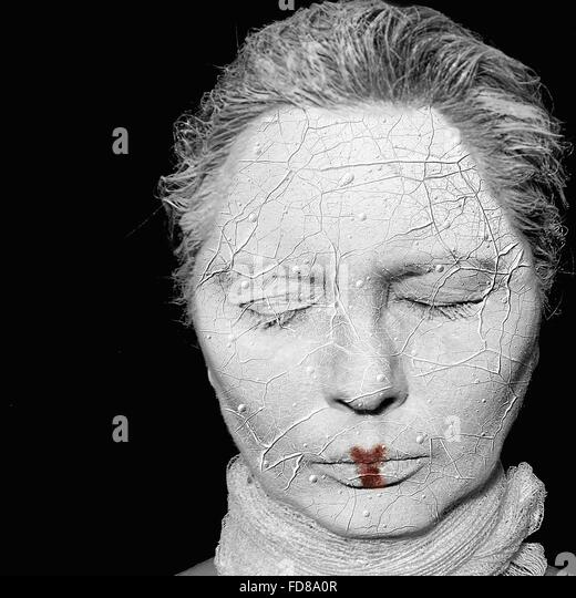 Close-Up Woman With Clay Covered Face Against Black Background - Stock-Bilder