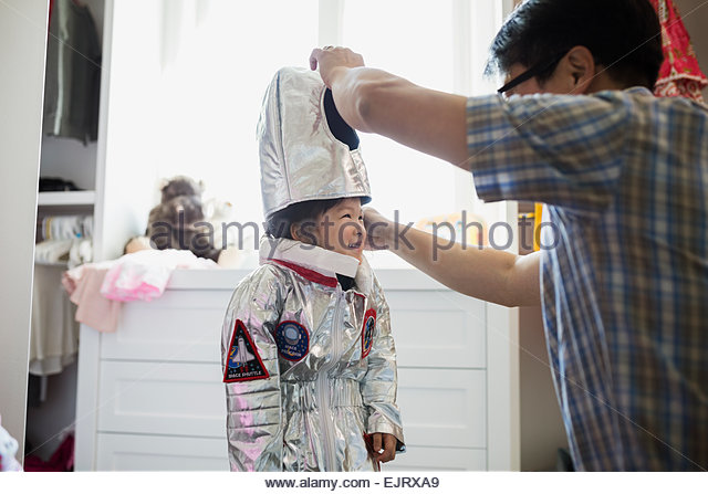 Grandfather putting astronaut costume on granddaughter in bedroom - Stock Image