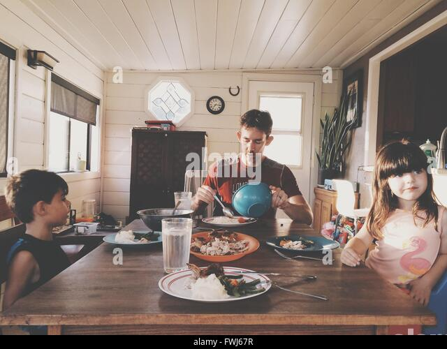 Father With Children Having Lunch At Home - Stock Image