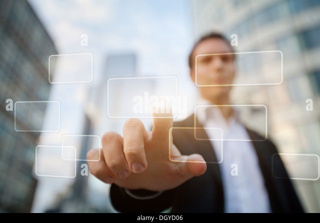 hand pushing on a touch screen interface on business buildings background - Stock Image