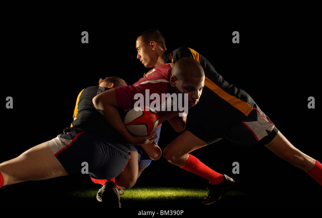 Rugby player tackled by two opponents - Stock Image