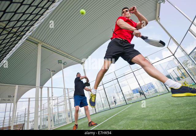 Wide angle paddle tennis couple smashing ball in court - Stock Image