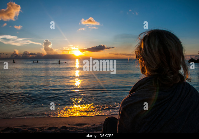 Woman watching the sunset in Guam, US Territory, Central Pacific, Pacific - Stock Image