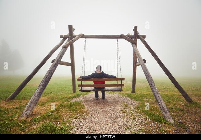 Sad man on the swing in mysterious fog - Stock Image