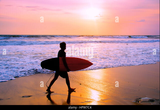 Surfer with surfboard walking on the sandy beach at sunset. Bali island, Indonesia - Stock Image