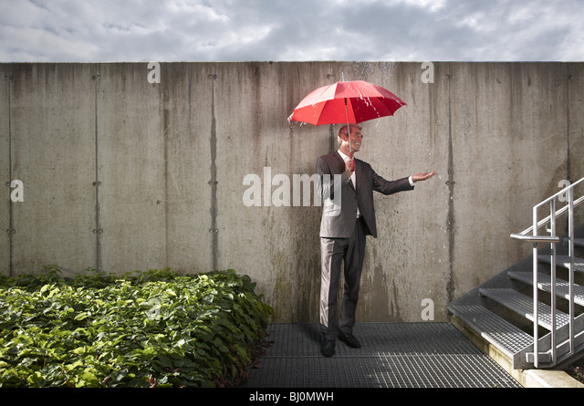 businessman with red umbrella protecting himself from rain - Stock Image
