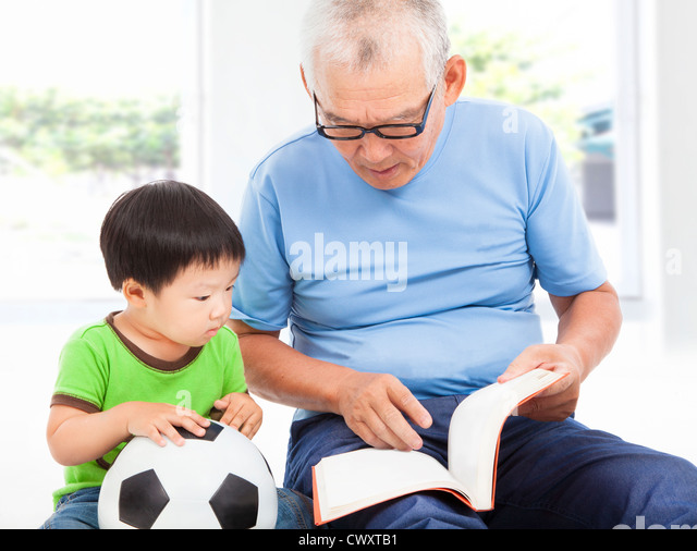 grandfather reading a story book for his grandson - Stock Image