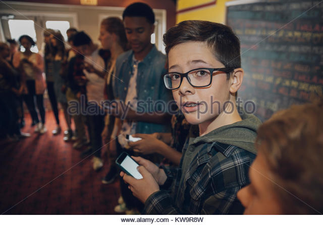 Portrait tween boy texting with smart phone,waiting in queue at movie theater - Stock Image