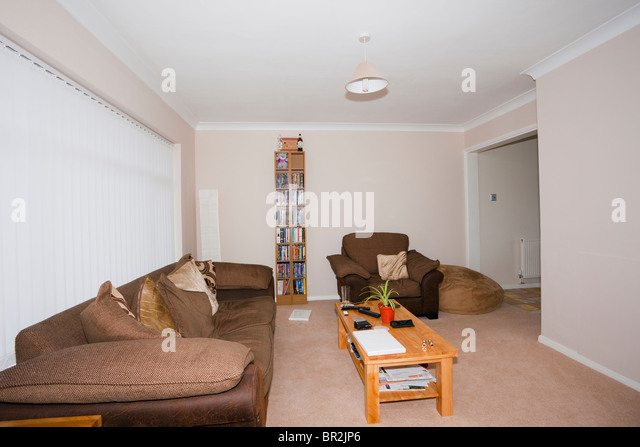 Sofa, chair and table in a tidy modern minimalist living room with window blinds closed in English home. England, - Stock Image