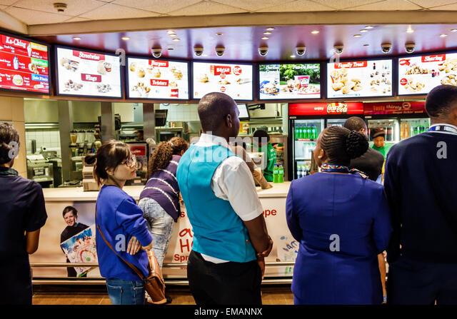 Johannesburg South Africa African O. R. Tambo International Airport terminal concourse gate area restaurant KFC - Stock Image