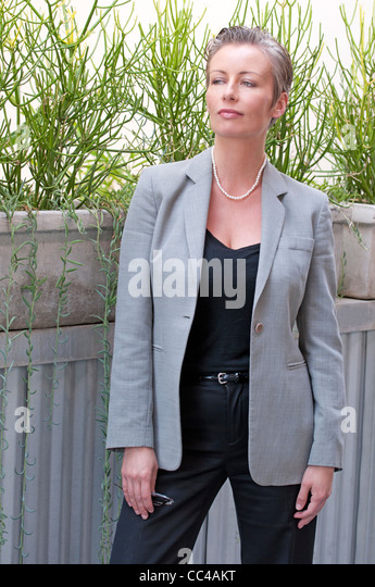 professional working woman stands near plants for business portrait holding glasses in gray and black wardrobe - Stock Image