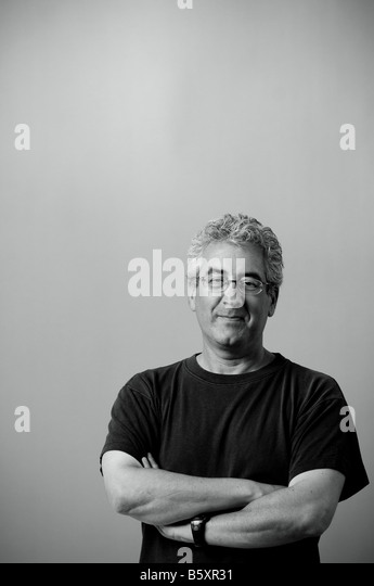 Proud smiling man with arms folded wearing black t-shirt. - Stock Image