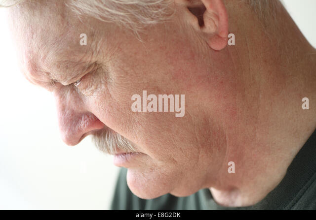 Downcast senior man with an expression of sadness, depression or grief - Stock Image