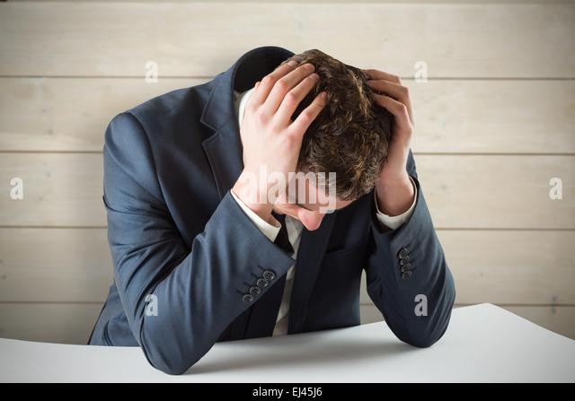 Composite image of businessman with head in hands - Stock-Bilder