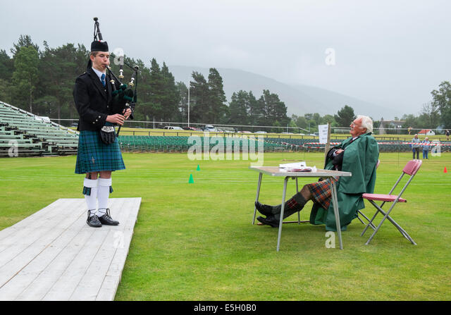 Piper and judge at Solo piping competition at Braemar Junior Highland Games in July in Scotland United Kingdom - Stock Image