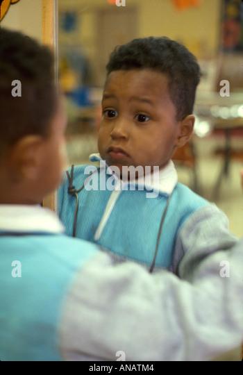 New Jersey Teaneck Black boy mirror reflection surprise startled - Stock Image