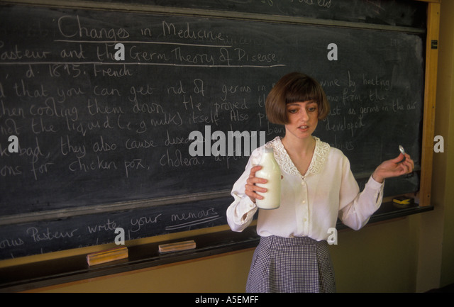 Greenford High school Middlesex young female teacher holds a bottle of milk to demonstrate changes in Medicine Pasteur - Stock Image