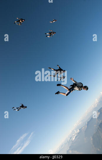 Skydivers follow eachother on a tracking skydive above Locarno, Switzerland - Stock Image