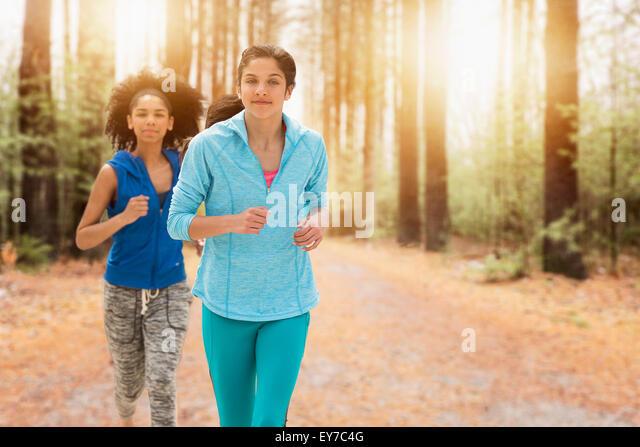 Portrait of teenage girls (14-15, 16-17) running - Stock Image