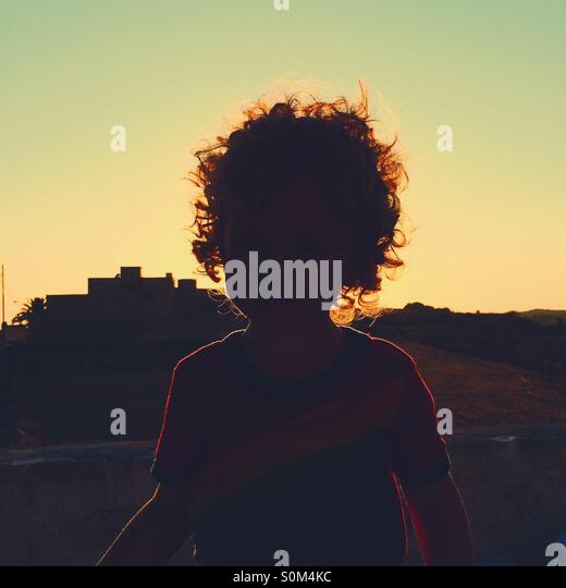Glowing silhouette of boy with sun going down in background - Stock Image