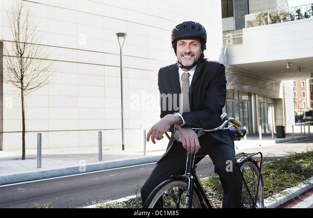Mid adult businessman sitting on bike, smiling - Stock Image