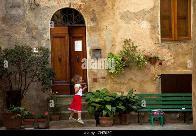 A young girl in a red dress leaves her home in Pienza, Italy. - Stock Image
