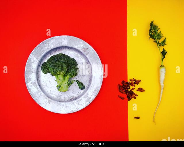 Simple Abstract Composition with Broccoli, White Carrot and Dried Chilliest on Red and Yellow Split Background - Stock Image